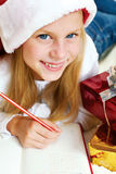 Little girl writing a letter to Santa Claus. Royalty Free Stock Photos