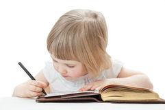 Little girl writing letters with a pen Stock Images