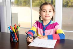 Little Girl Writing Letters. Little Girl Is Practicing Writing Letters Royalty Free Stock Image