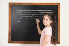 Little girl writing music notes on blackboard stock photography