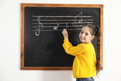 Little girl writing music notes on blackboard royalty free stock photo