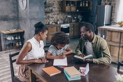 Little girl writing at notebook with parents. Little girl writing at her notebook at the kitchen table with her parents sitting beside her Stock Images