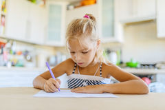 Little girl writing with pen in notebook Stock Photography