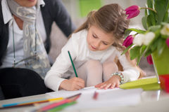 Little girl writing in the presence of his grandmother Stock Images