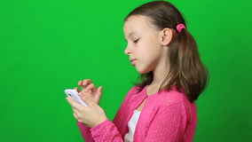 Little girl writing short message on mobile phone stock footage