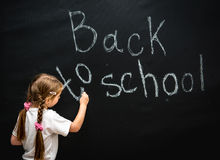 Little girl wrote in chalk on black chalkboard Stock Photography