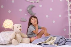 Little girl yawning on bed at home. Time to sleep stock photos