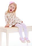 Little girl yawns while sitting on the couch Royalty Free Stock Photography