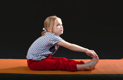 Little girl 5-7 years, doing exercises on the mat for yoga. Pull Stock Photos