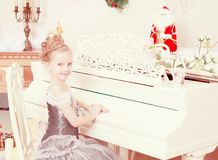 Little girl playing on a white Grand piano. Royalty Free Stock Photos