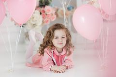 Cute six year old girl in pink dress with pink balloons in the shape of heart. A little girl of 6 years with long curly hair, dressed in a pink dress and white Royalty Free Stock Image