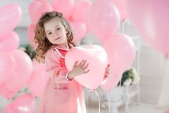 Cute six year old girl in pink dress with pink balloons in the shape of heart. A little girl of 6 years with long curly hair, dressed in a pink dress and white Stock Photos