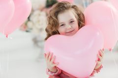 Cute six year old girl in pink dress with pink balloons in the shape of heart. A little girl of 6 years with long curly hair, dressed in a pink dress and white Stock Images