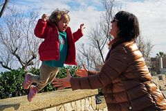 Little girl 2-3 years old happily jumping on hands to mom royalty free stock photo