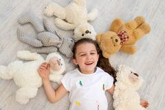 A little girl 5-6 years old lies among Teddy bears