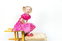 Little girl 3 years old in a red dress with bows in her hair. Beautiful girl in a beautiful fluffy dress posing against a white wall royalty free stock image