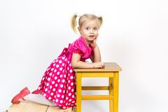 Little girl 3 years old in a red dress with bows in her hair. Beautiful girl in a beautiful fluffy dress posing against a white wall royalty free stock photo