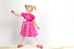 Little girl 3 years old in a red dress with bows in her hair. Beautiful girl in a beautiful fluffy dress posing against a white wall royalty free stock photography