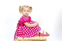 Little girl 3 years old in a red dress with bows in her hair. Beautiful girl in a beautiful fluffy dress posing against a white wall stock images