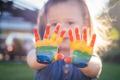 Little girl 2-4 years old shows her palms painted in rainbow colors standing against sunlight