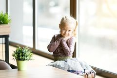 A beautiful child is sitting near a large window. A little girl, 4-5 years old, is sitting on the windowsill of a large window in a cafe stock photography