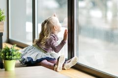 A beautiful child is sitting near a large window. A little girl, 4-5 years old  is sitting on the windowsill of a large window in a cafe stock image