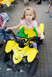 Little girl on yellow ATV Stock Photography