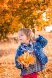 Little girl with yellow autumn golden leaves. Child play outdoors in the park. Holding hand behind the head Stock Photography