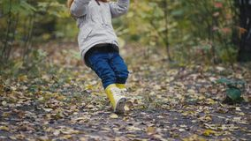 Little girl in yellow boots plays with rope at playground on autumn park stock video