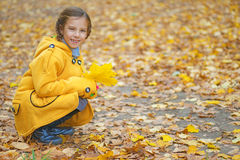 Little girl in yellow coat collects Royalty Free Stock Photo