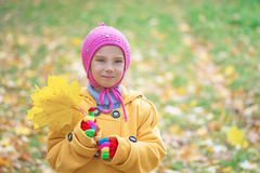 Little girl in yellow coat collects Royalty Free Stock Photos