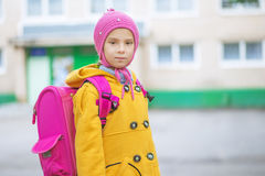 Little girl in yellow coat and pink Royalty Free Stock Photography