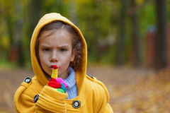 Little girl in yellow coat put Royalty Free Stock Photography