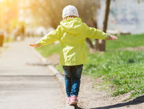 Little girl in yellow coat walking in park Royalty Free Stock Photo
