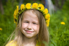 Little girl in yellow dandelion wreath Stock Image