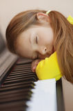Little girl in yellow dress asleep. Beautiful little girl in yellow dress asleep on piano Stock Photography
