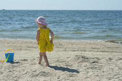 Little girl in a yellow dress on the beach Royalty Free Stock Photography