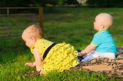 Little girl in yellow dress and boy in blue shirt crawling on grass royalty free stock images