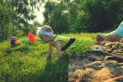 A little girl in a yellow dress crawls on grass royalty free stock photos