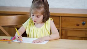 Little girl in a yellow dress with crayons draws on paper. On a wooden table stock video