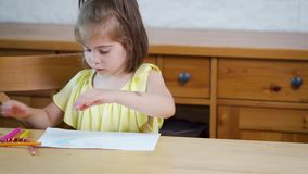 Little girl in a yellow dress with crayons draws on paper. On a wooden table stock video footage