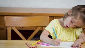 Little girl in a yellow dress with crayons draws on paper. On a wooden table stock footage