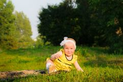 Little girl in a yellow dress on a green grass royalty free stock photography