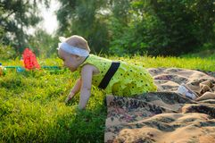 Little girl in a yellow dress creeps on a green grass stock image