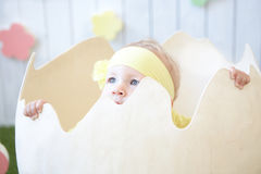 Little girl in yellow dress with decoration hiding into the eggs Stock Images