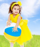 Little girl in yellow dress holding a ball Royalty Free Stock Photo
