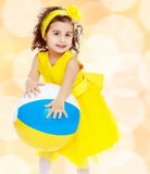 Little girl in yellow dress holding a ball Stock Photo