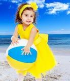 Little girl in yellow dress holding a ball Stock Photos
