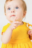 Little girl in the yellow dress on a light background.  Royalty Free Stock Photography