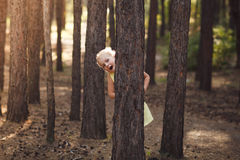 Little girl in yellow dress peeking from behind the trees in th. E summer forest royalty free stock photography